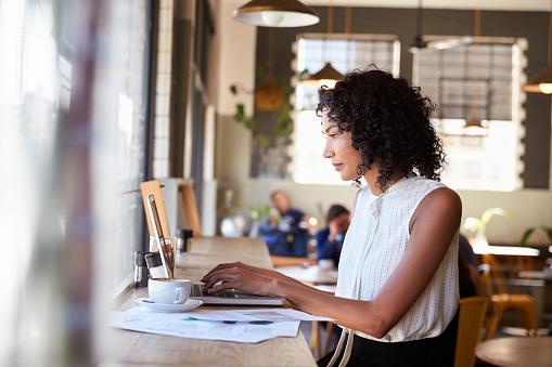 Businesswoman By Window Working On Laptop In Coffee Shop 672497086