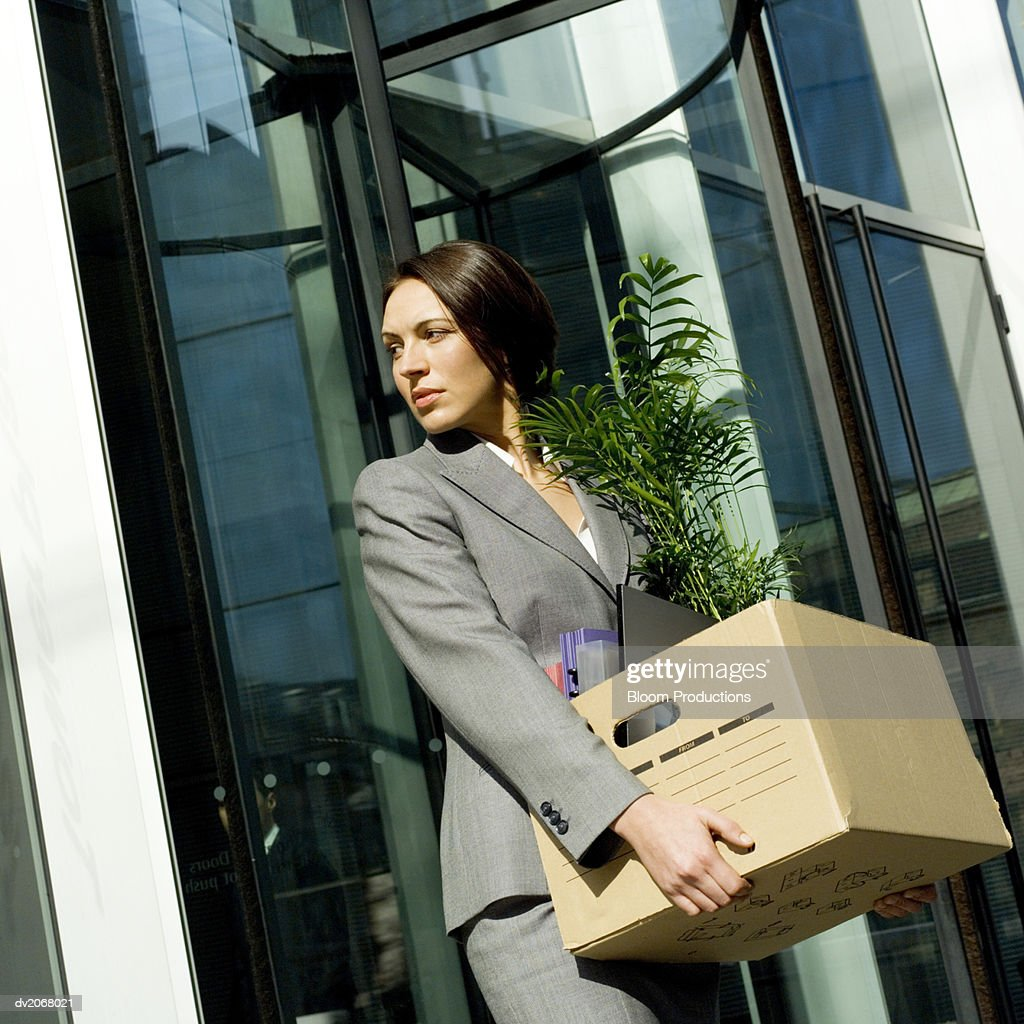 Businesswoman Carries a Cardboard Box of Her Possessions Out of Her Office : Stock Photo