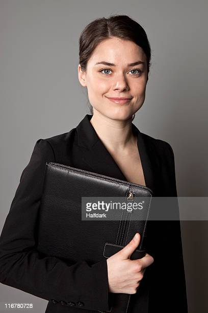 A businesswoman carrying an a leather padfolio