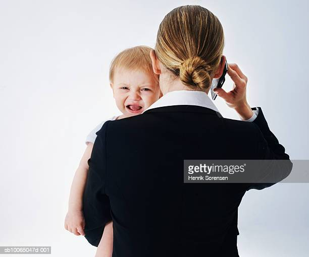 Businesswoman carrying baby boy, (12-15 months ) using mobile phone