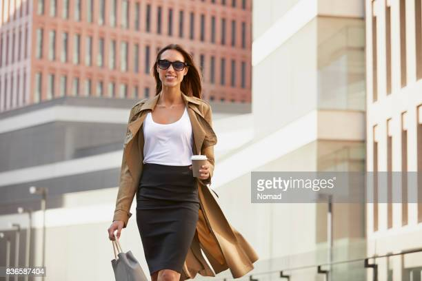 Businesswoman carrying bag and cup in city