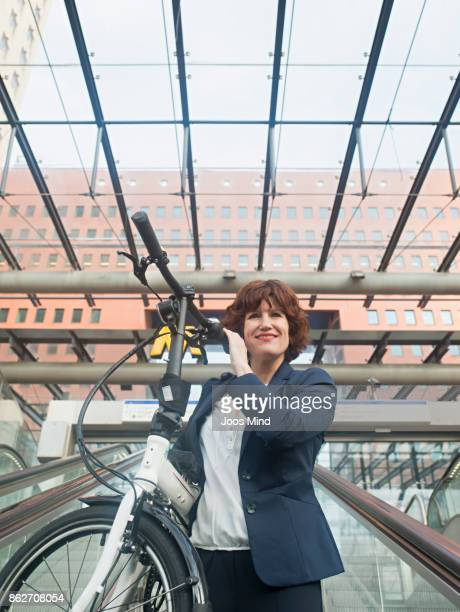 businesswoman carrying bike on shoulder, using escalator to subway