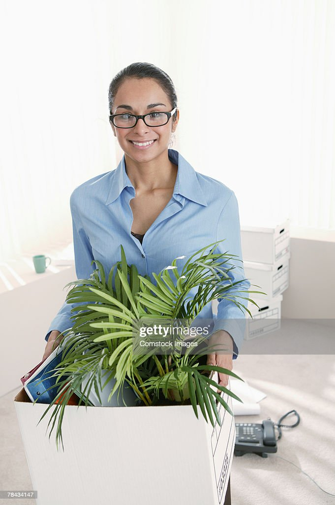 Businesswoman carrying box of stuff out of office : Stockfoto
