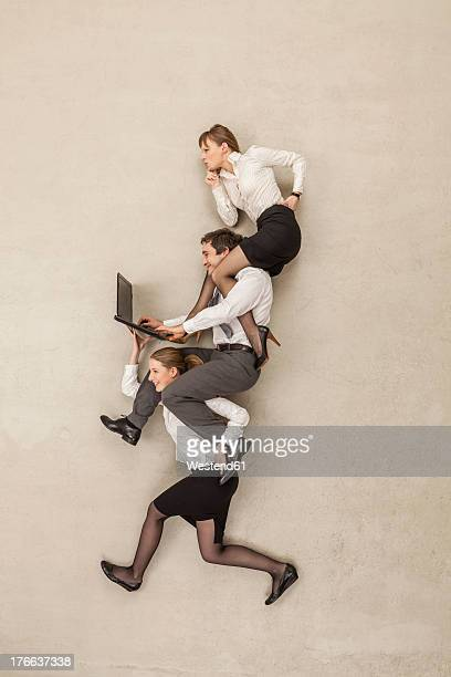 Businesswoman carrying business people using laptops on shoulders