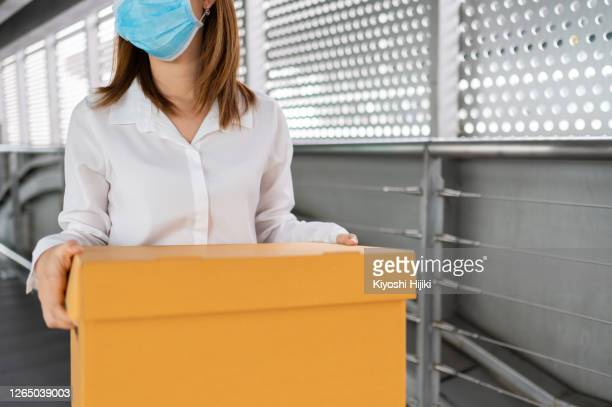 businesswoman carrying cardboard box with personal items after being fired due to pandemic and company bankruptcy - downsizing unemployment stock pictures, royalty-free photos & images