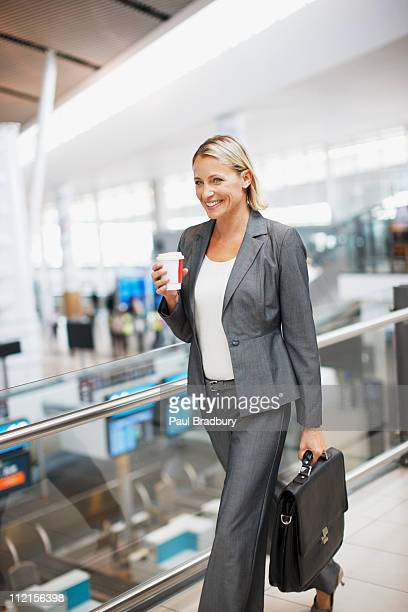 Businesswoman carrying coffee in airport