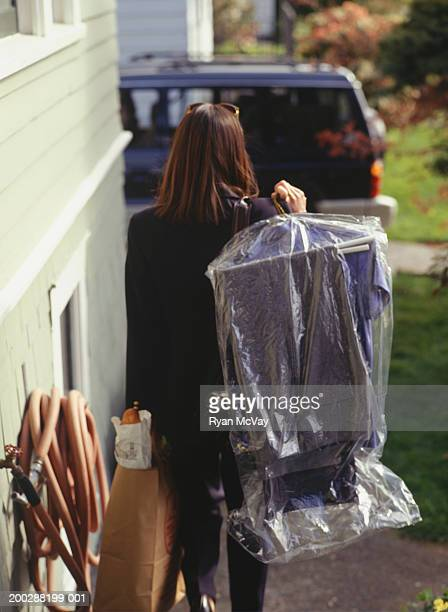 Businesswoman carrying groceries and dry cleaning to car