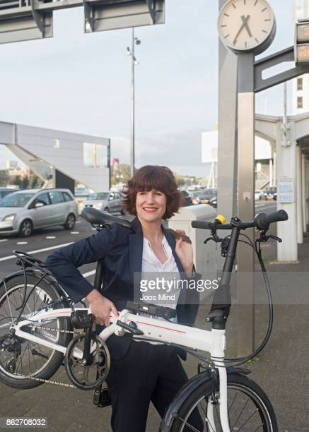 businesswoman carrying her bike to the subway station