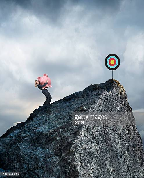 businesswoman carrying piggy bank up mountain to reach financial goals - sports target stock photos and pictures