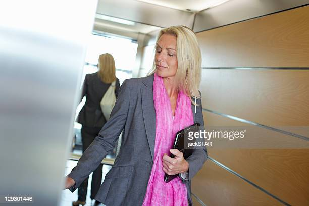 Businesswoman carrying tablet in office