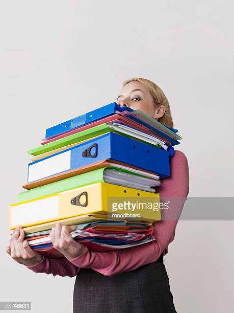 Businesswoman Carrying Too Many Binders