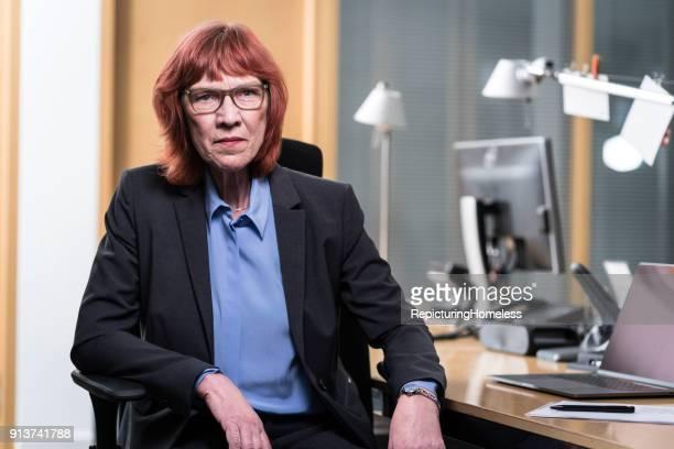 Eine Geschäftsfrau sitzt locker in ihrem Stuhl und schaut in die Kamera