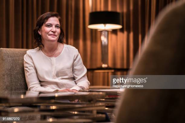 Geschäftsfrau sitzt in der Hotellobby und schaut in die Kamera
