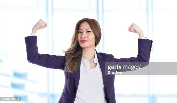 businesswoman celebrating business success and flexing muscles - flexing muscles stock pictures, royalty-free photos & images