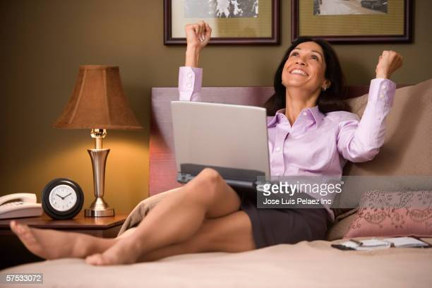 Businesswoman celebrating in her hotel room