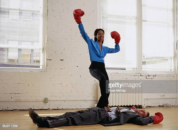 businesswoman celebrating knocking out an opponent - mixed boxing stock photos and pictures