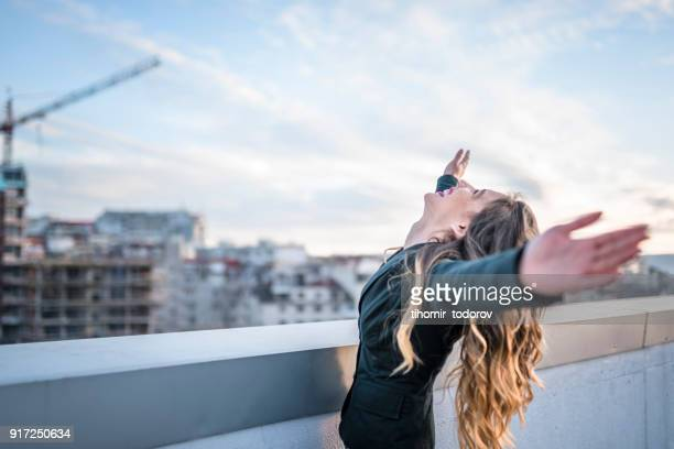 Businesswoman celebrating on urban rooftop