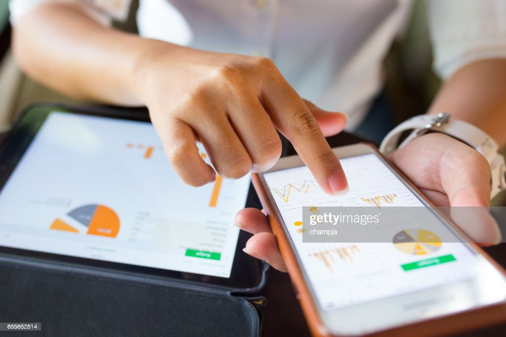 Businesswoman check data in smartphone and tablet : Stock Photo