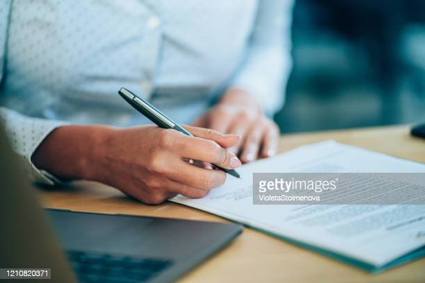businesswoman checking agreement before signing. - agreement stock pictures, royalty-free photos & images