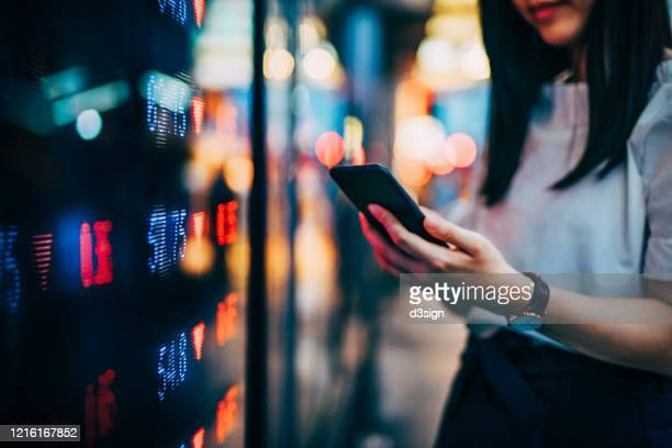 businesswoman checking financial trading data on smartphone by the stock exchange market display screen board in downtown financial district showing stock market crash sell-off in red colour - hang seng index stock pictures, royalty-free photos & images