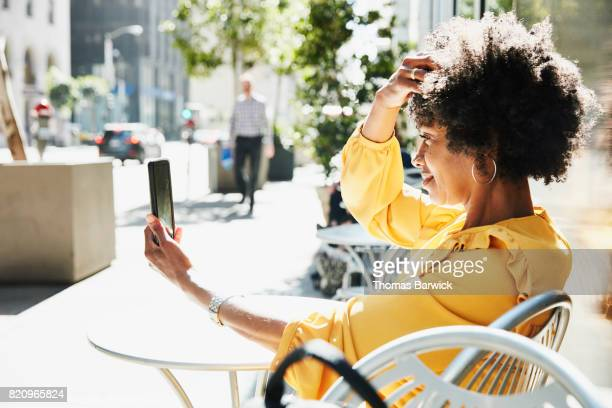 businesswoman checking hair with smartphone while seated at outdoor cafe - yellow dress stock pictures, royalty-free photos & images