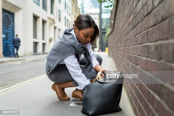 businesswoman checking her purse in a hurry - borsetta da sera foto e immagini stock