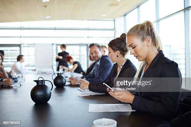 Businesswoman checking her smartphone at meeting