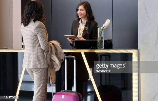 geschäftsfrau prüft in der hotelaufnahme - gast stock-fotos und bilder