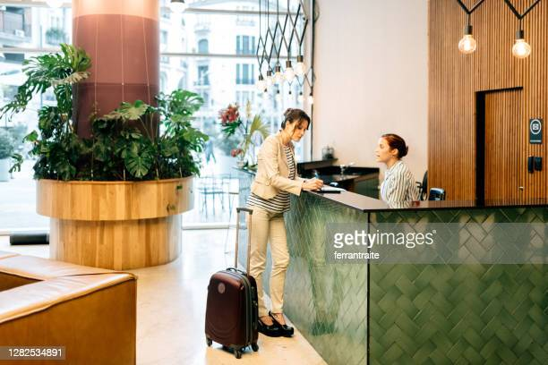 businesswoman checking in at hotel reception - form filling stock pictures, royalty-free photos & images