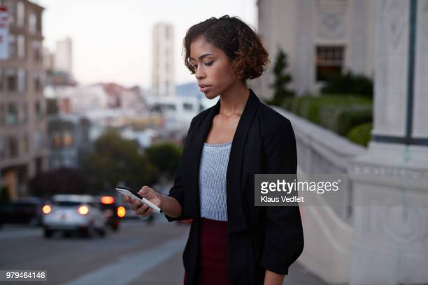Businesswoman checking phone while on the street in the evening