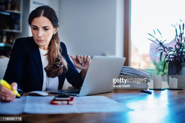 businesswoman checking plan with laptop at home office. - 在宅勤務 ストックフォトと画像