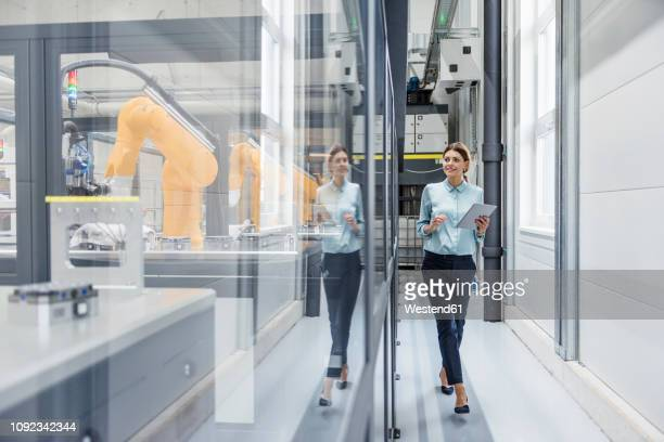 businesswoman checking robots with digital tablet in high tech company - kommerzielle herstellung stock-fotos und bilder