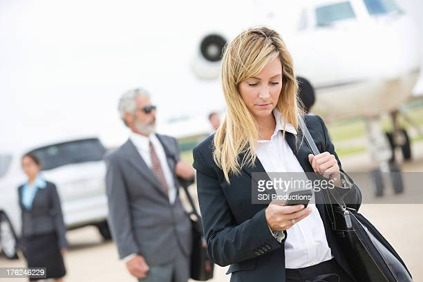 Businesswoman checking smart phone after deboarding private company jet