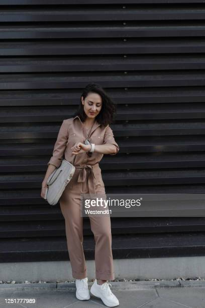 businesswoman checking smart watch while standing against black shutter - jumpsuit stock pictures, royalty-free photos & images