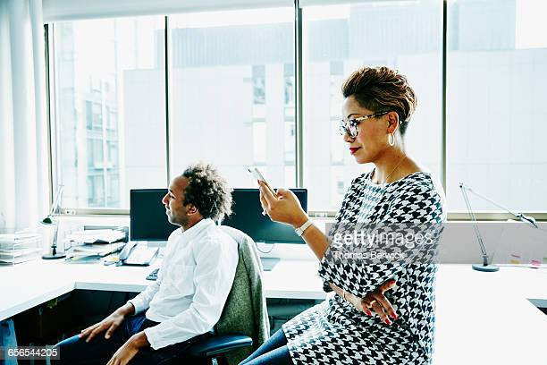 Businesswoman checking smartphone during meeting
