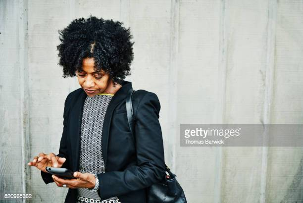 Businesswoman checking smartphone on city street