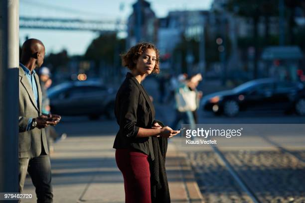 Businesswoman checking smartphone while waiting for the tram in San Francisco