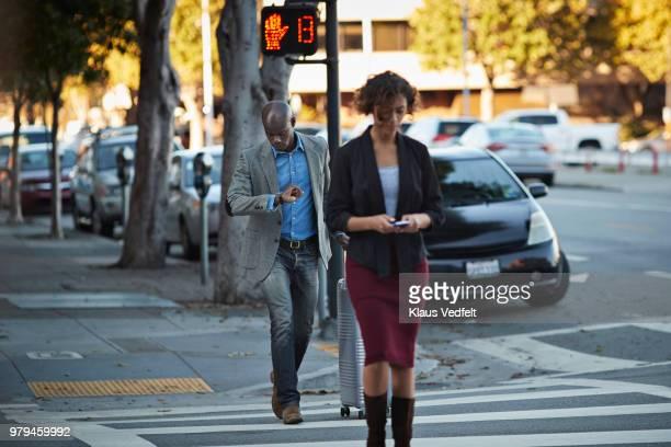 businesswoman checking smartphone while walking on pedestrian crossing - cruzar fotografías e imágenes de stock