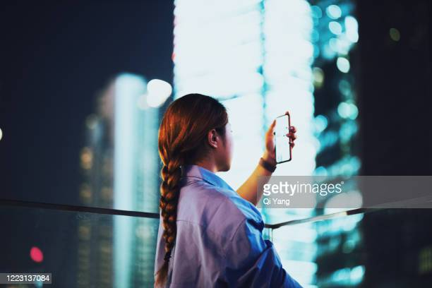 businesswoman checking the mobile phone in the downtown district at night - development stock pictures, royalty-free photos & images