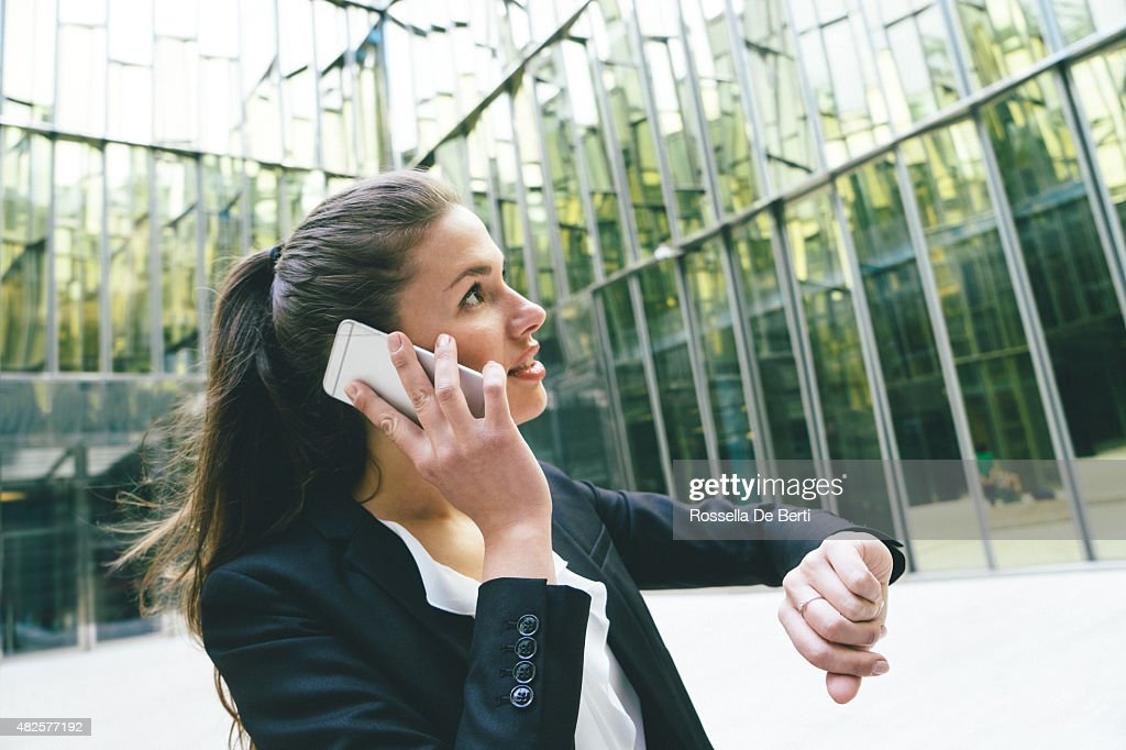Businesswoman Checking Time And Making A Phone Call : Stock Photo
