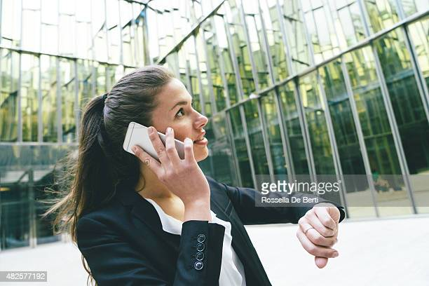 businesswoman checking time and making a phone call - time management stock photos and pictures