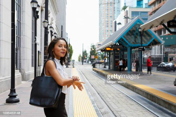 businesswoman checking time by light rail line - black purse stock pictures, royalty-free photos & images