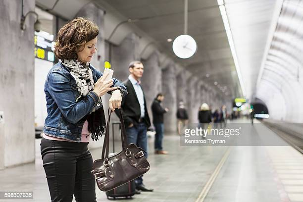 Businesswoman checking time while waiting at railroad station platform