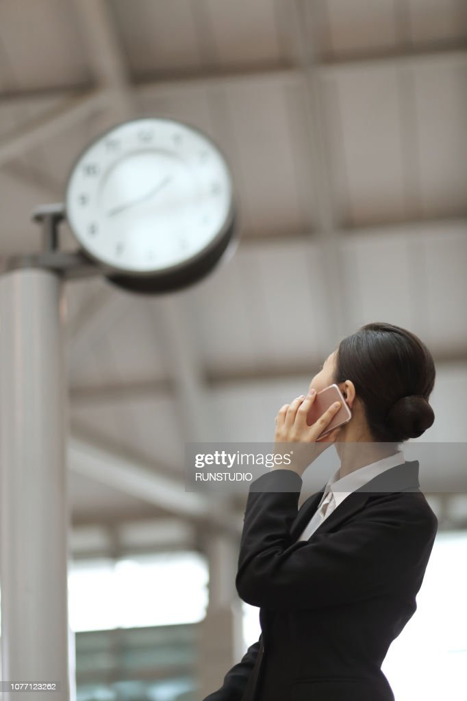 Businesswoman checking time with smartphone in airport : Stock Photo