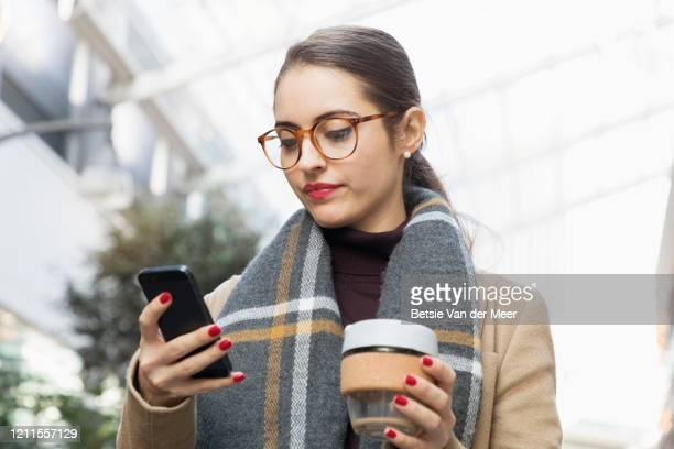 businesswoman checks her phone while walking in city street. - portable information device stock pictures, royalty-free photos & images