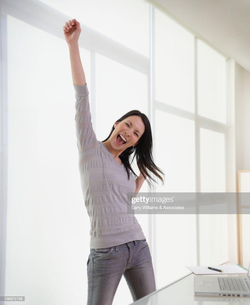 Businesswoman cheering in office : Stockfoto