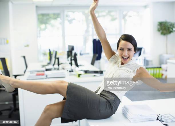 Businesswoman cheering in office