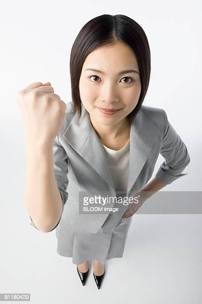 Businesswoman clenching fist, portrait, high angle view, studio shot