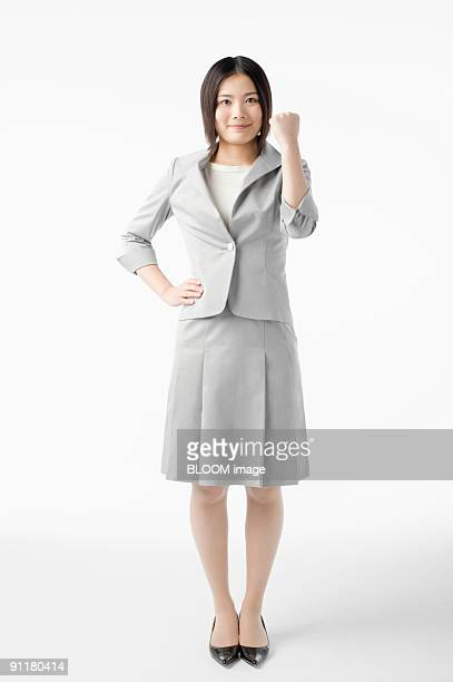Businesswoman clenching fist, portrait, studio shot