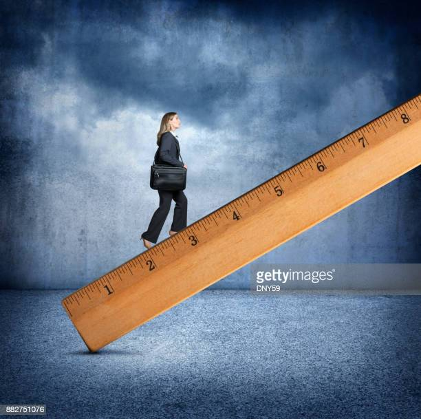 Businesswoman Climbing A Large Wooden Ruler